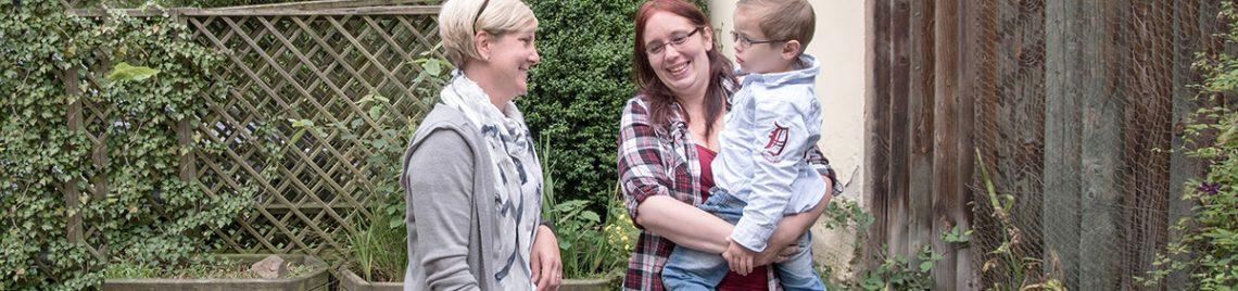 Zwei Frauen mit Kind auf dem Arm